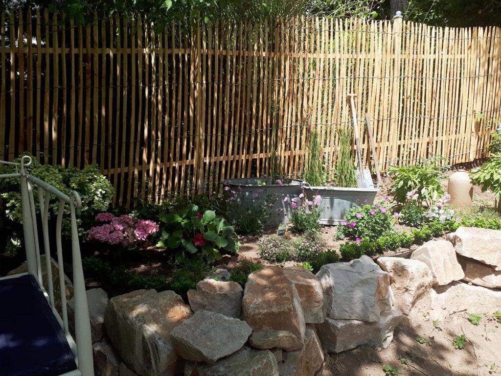 Der Staketenzaun passt mit seiner Natürlichkeit gut in den romantischen Garten