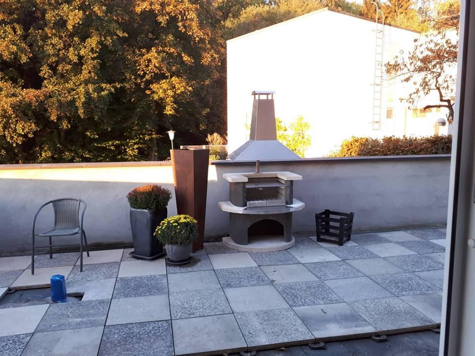 Etwa mittig am Rand der Terrasse wurde der passende Grillkamin platziert.