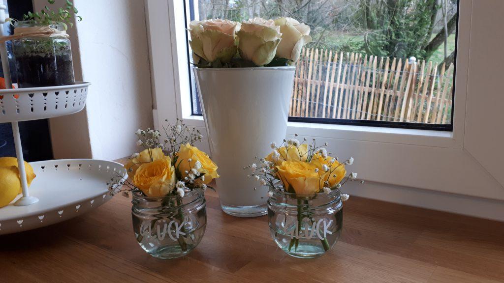 Die leeren Gläser der Glück-Marmelade als kleine Vasen oder eben Gläser voll Glück