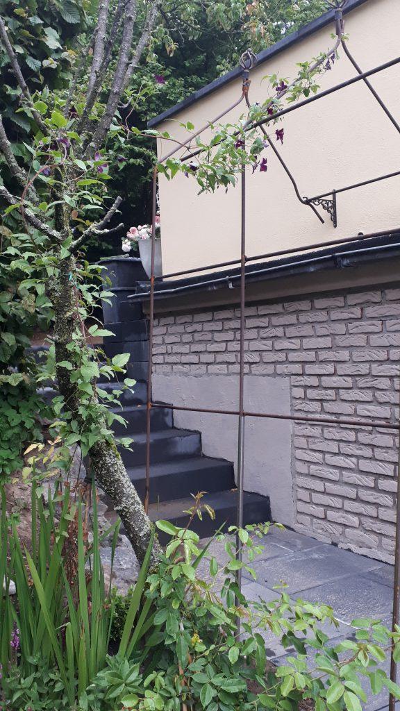 Rankbogen mit Clematis über Treppenabgang an der Garage
