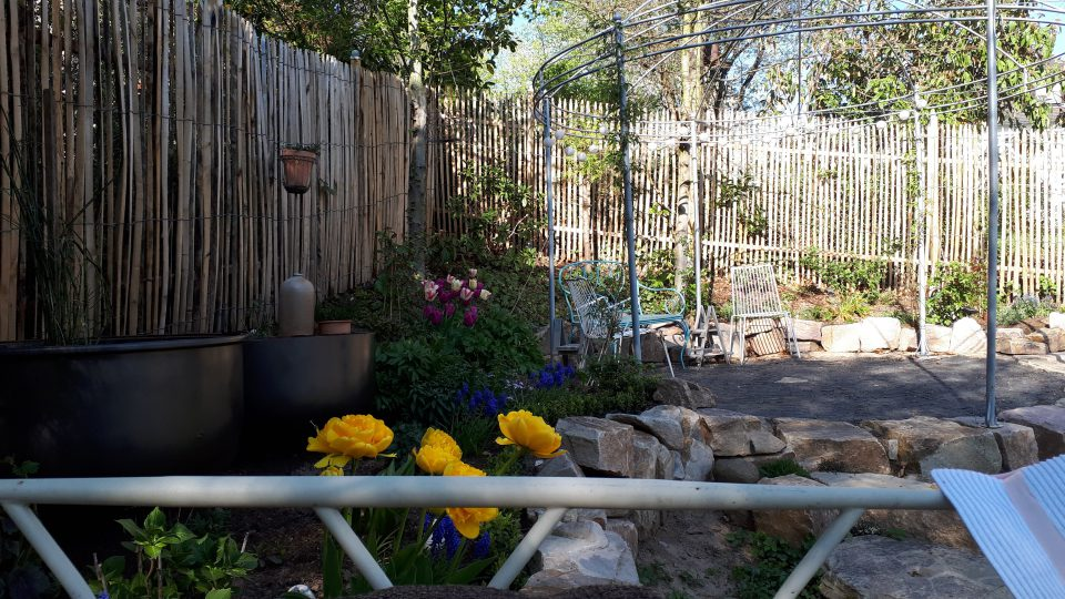 Blick auf das Staudenbeet und Rosenpavillon, vom Gartenbett aus