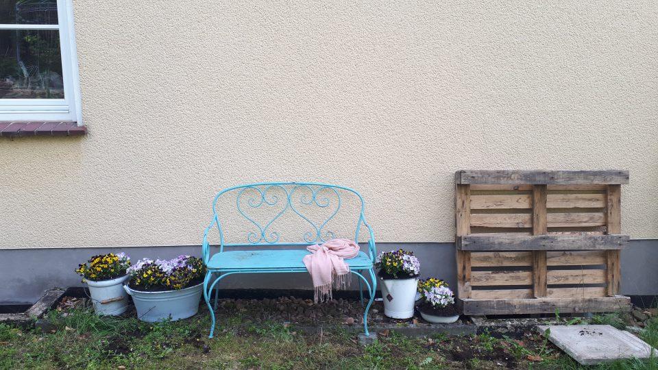 Die blaue Gartenbank an der Hauswand