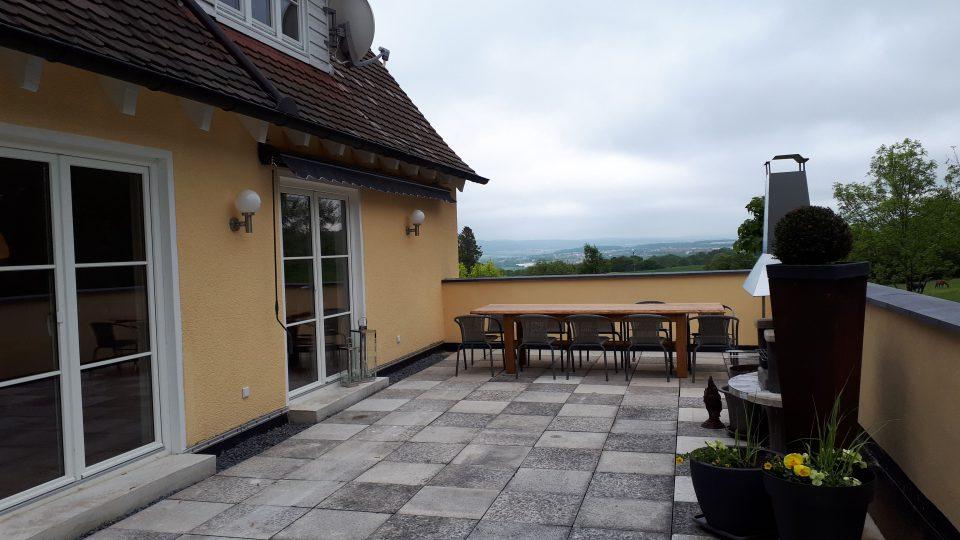 Die sanierte Terrasse mit den klassischen Kugelleuchten an der frisch gestrichenen Fassade unseres 50er Jahre Hauses.