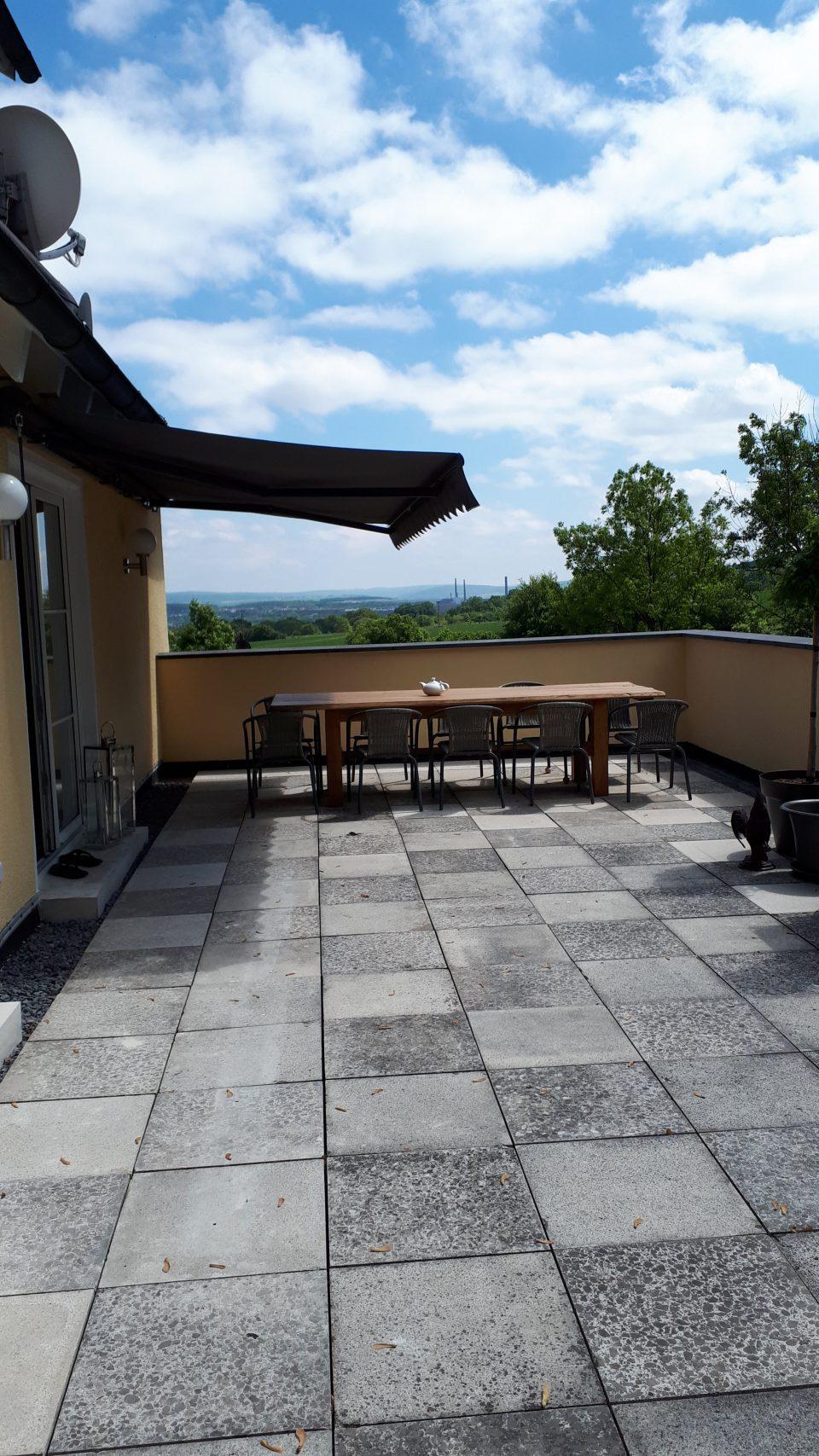 Die breite Markise dient als Sonnenschutz der Terrasse