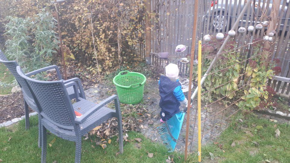 Ein Gartenzwerg bei der Arbeit im herbstlichen Garten