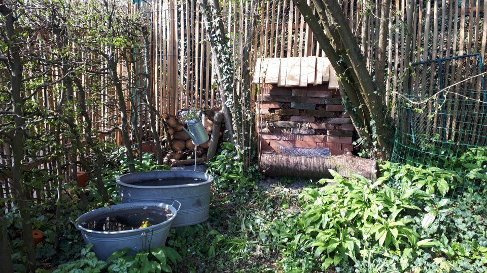 Das neu gebaute Insektenhotel mit Regenschutz vor dem Staketenzaun.