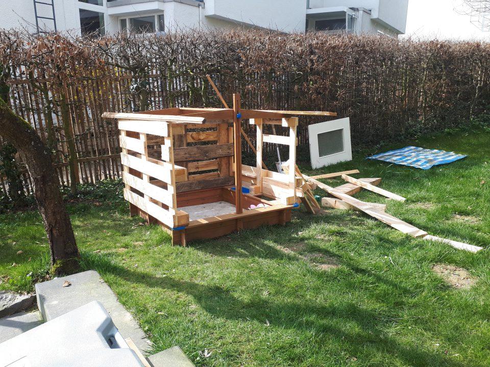 Der Sandkasten und Paletten bilden die Grundlage für unser Baumhaus.