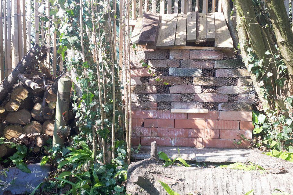 Das Insektenhotel aus Backsteinen ist mit Maschendraht am Staketenzaun befestigt.