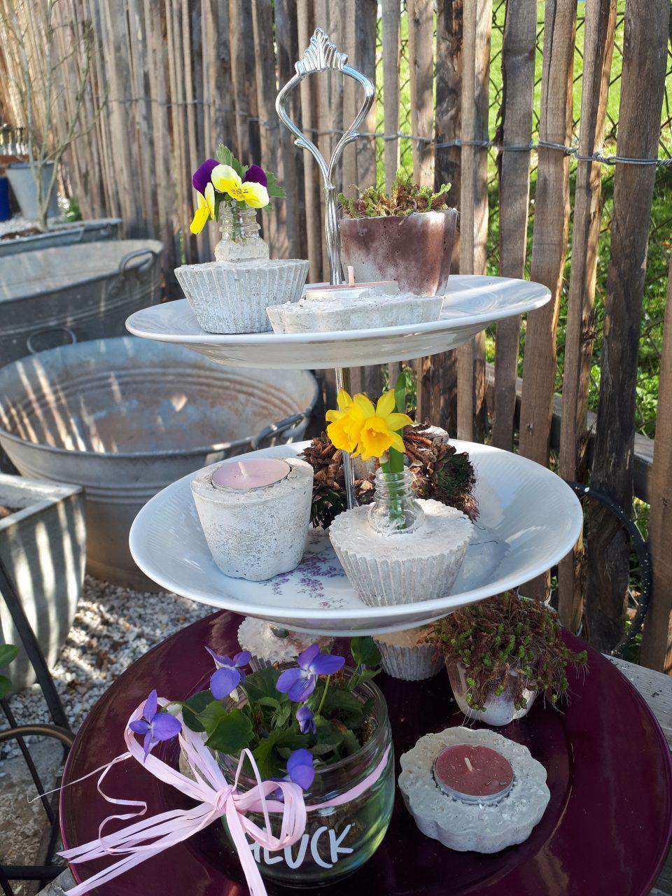Die Törtchen aus Beton mit den verschiedenen Formen dienen als Vasen, Teelichthalter oder sind bepflanzt.