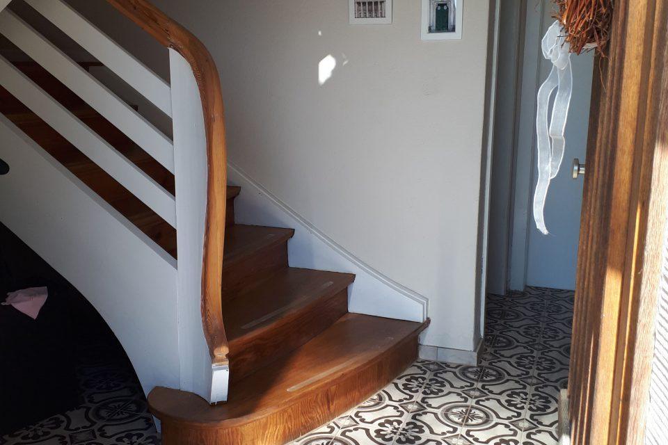 Der Eingangsbereich im Kellergeschoss nach der Sanierung mit spanischen Fliesen und geölter Holztreppe.
