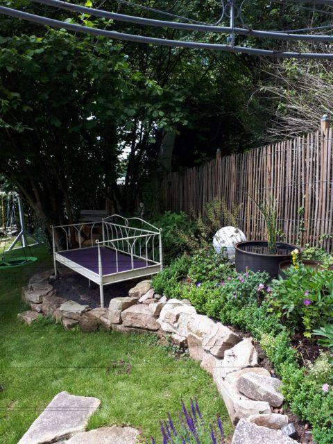 Ein Gartenbett im Halbschatten mit benachbartem Wasserspiel ist ein Kleinod im romantischen Garten. Es lädt zum Lesen eines Gartenkrimi eins