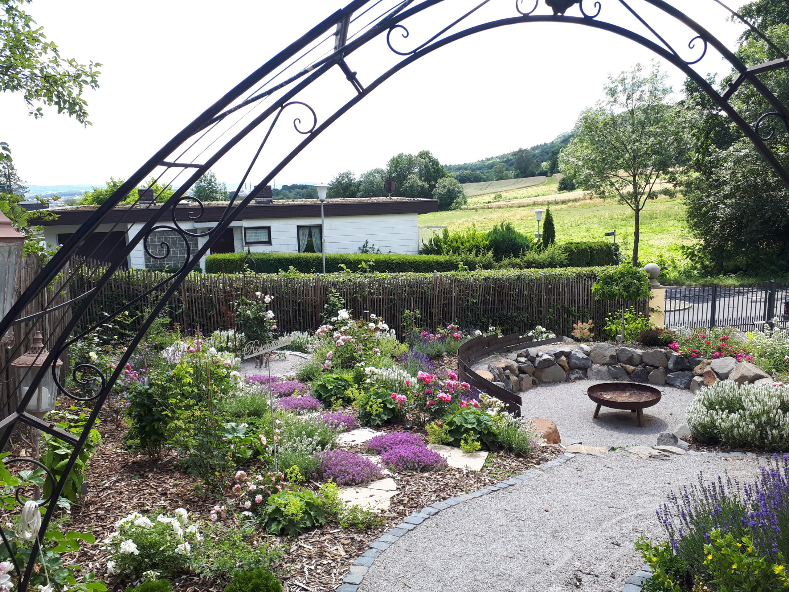 Der Romantikgarten wurde geplant und im Sommer 2019 angelegt. Hier sind der Blick in den Rosengarten sowie Senkgarten mit Feuerschale zu sehen.