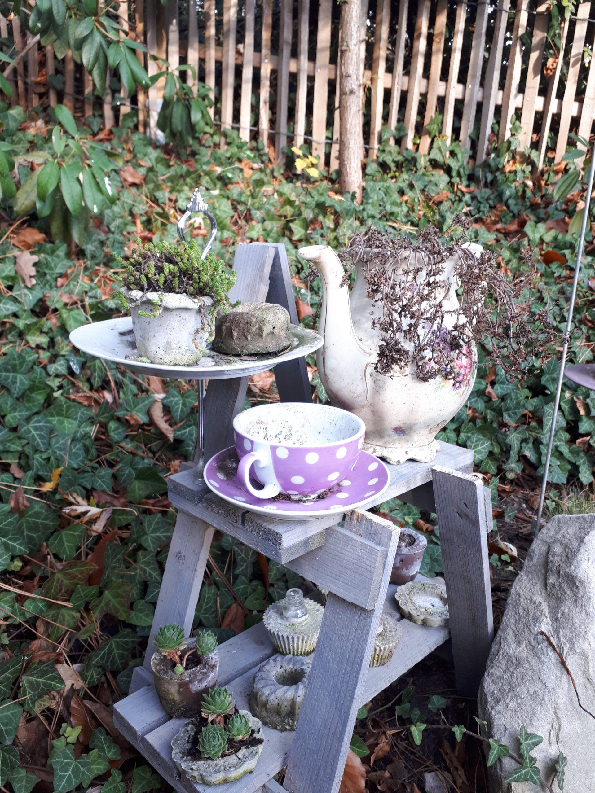 Wie eine gedeckte Kaffeetafel ist die alte Tasse mit der bepflanzten Kanne und den Törtchen aus Beton arrangiert.