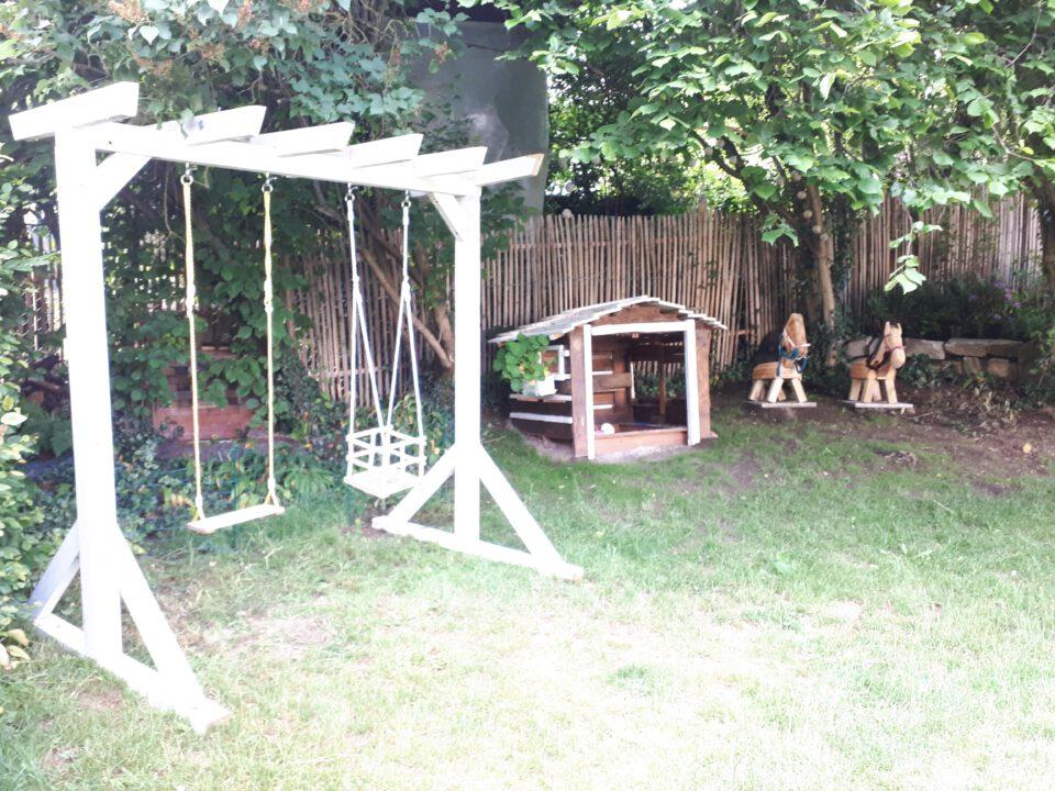 Neben dem Baumhaus stehen nun die Schaukelpergola und die Holzpferde. Es ist ein richtiger Abenteuerspielplatz geworden.