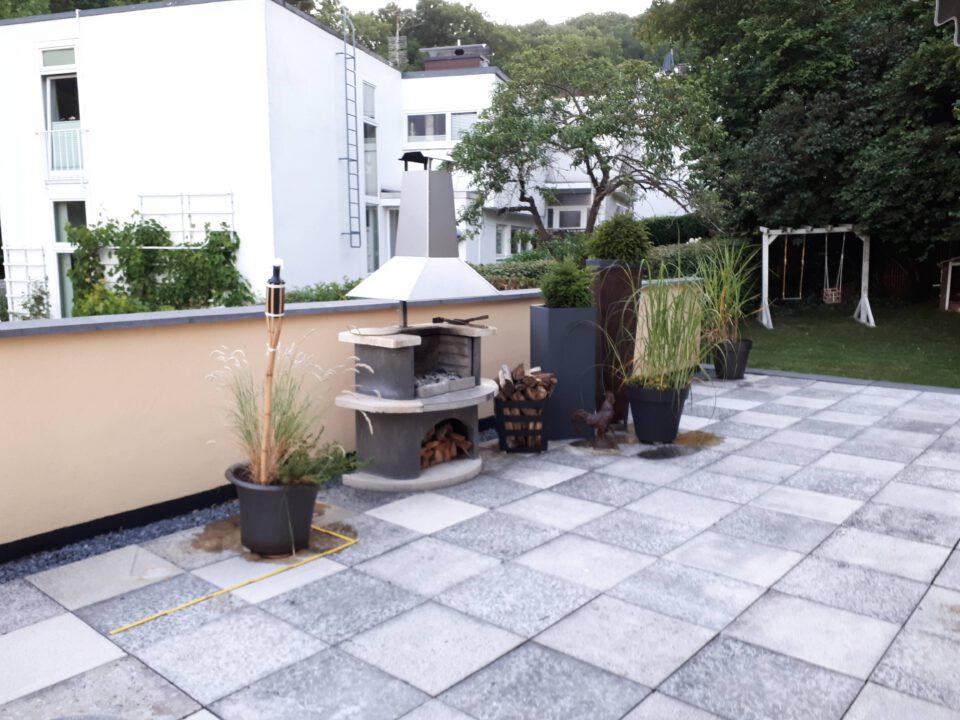 Der Grillkamin auf der Terrasse mit Blumenkübeln