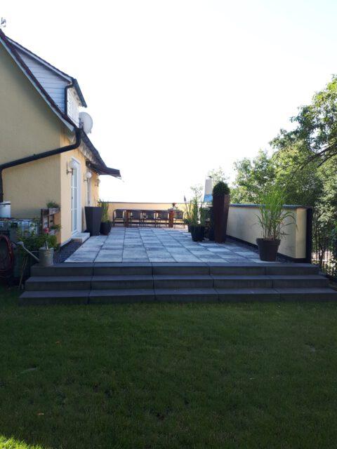 Der breite Treppenabgang der neu gestalteten Terrasse lässt sie noch großzügiger wirken