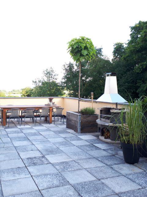 Die neu gestaltete Terrasse mit Hochbeet und Grillkamin
