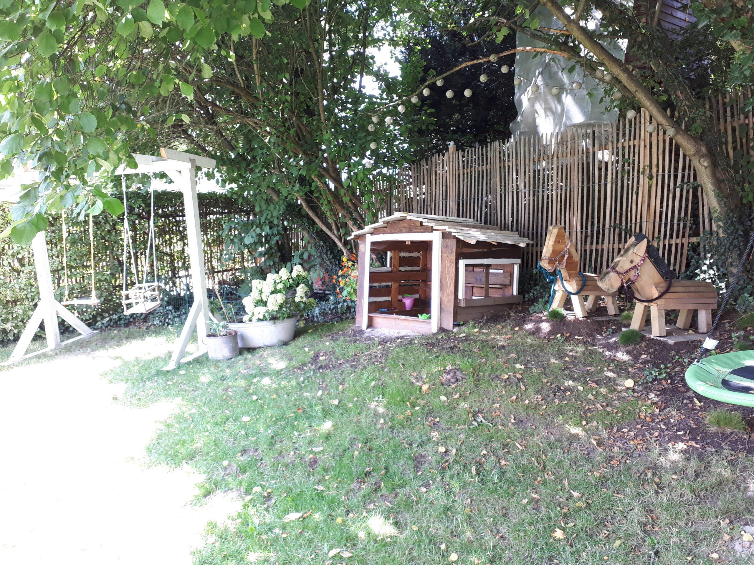 Unser Abenteuerspielplatz im Garten mit Baumhaus, Holzpferden und Schaukelpergola.