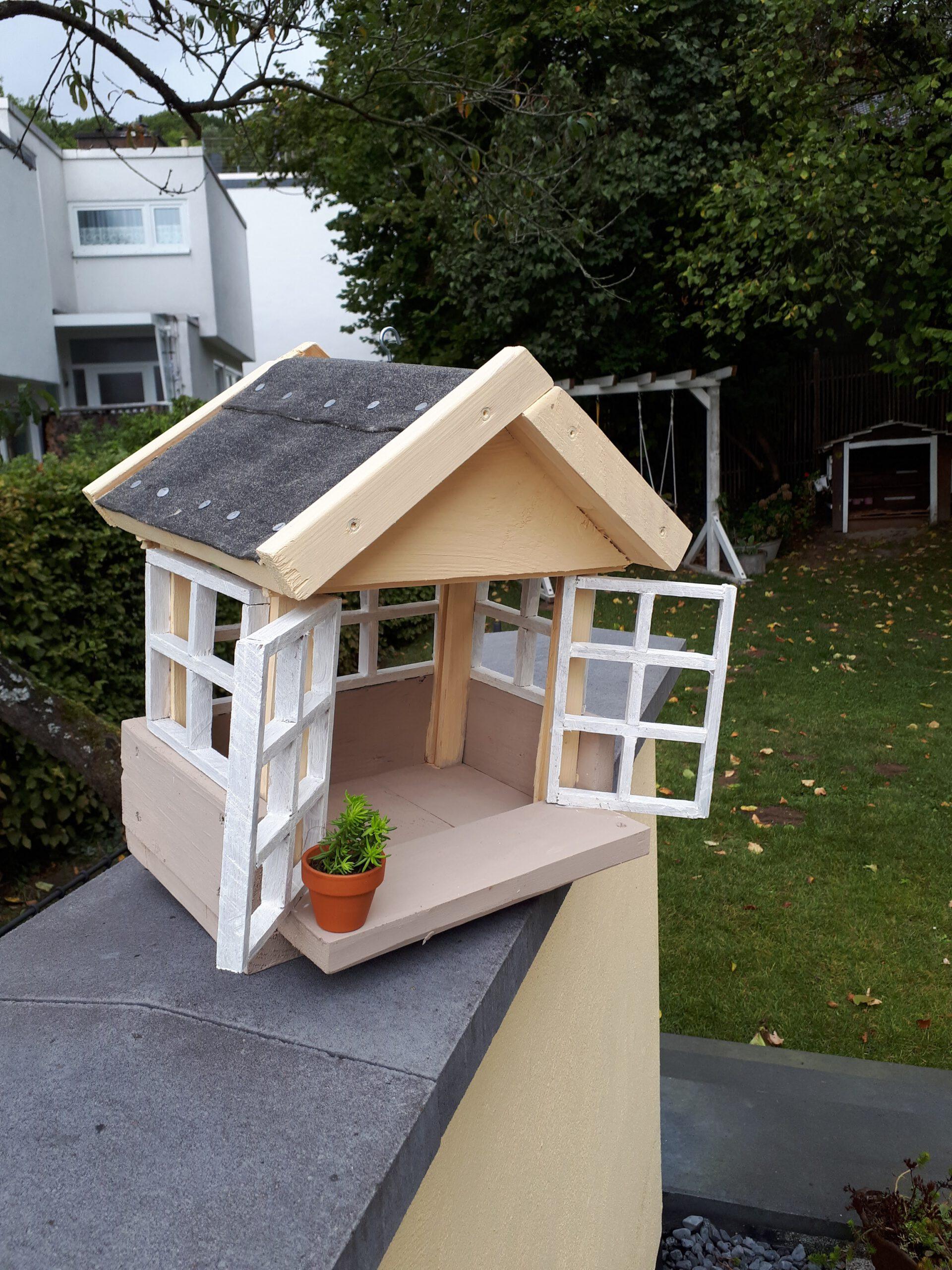 Das selbst gebaute Vogelfutterhaus hängt im Pfirsichbaum neben der Terrasse.