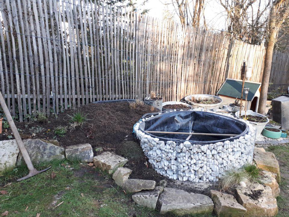 Der selbst gebaute Garten Whirlpool mit frisch aufgeschütteter Erde zum Bepflanzen