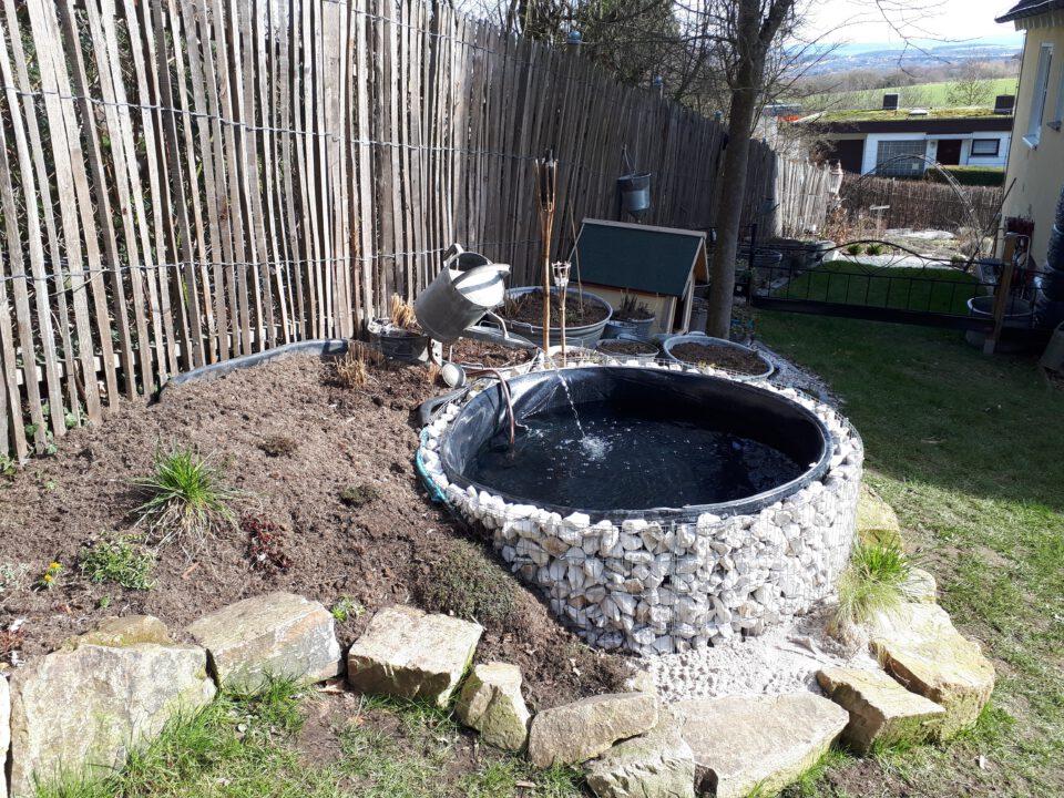 Der frisch gefüllte Garten Whirlpool mit Wasserspiel aus alter Zinkgießkanne